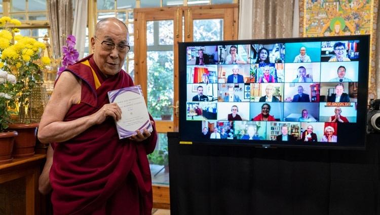 Его Святейшество Далай-лама держит экземпляр книги «Наука и философия в индийской буддийской классической литературе, том 2: Сознание», фотографируясь у экрана с участниками издания. Дхарамсала, штат Химачал-Прадеш, Индия. 13 ноября 2020 г. Фото: дост. Тензин Джампхел.